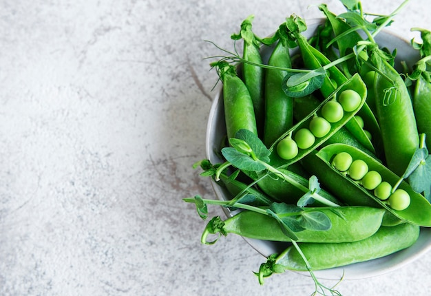 Fresh green peas pods and green peas with sprouts on concrete background