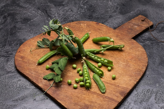 Fresh green peas pods on a wooden board.