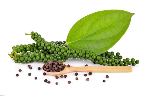 Fresh green peppercorns and black peppercorns isolated on white