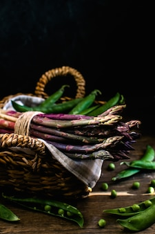 Fresh green and purple asparagus, green peas in wicker basket