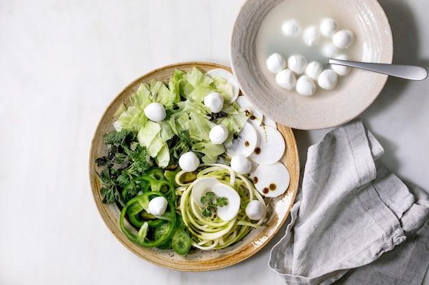 Свежие зеленые сырые овощи и зелень, спагетти, цукини и шарики из моцареллы, вид сверху