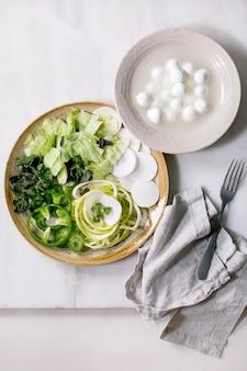 Свежие зеленые сырые овощи и зелень, спагетти, цукини, белый редис, зеленый перец, ледяной салат, шарики моцареллы для приготовления салата на ужин. керамическая тарелка на белом мраморном столе. плоская планировка, копия пространства