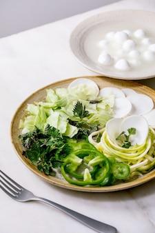 Свежие зеленые сырые овощи и зелень, спагетти, цукини, белый редис, зеленый перец, ледяной салат, шарики моцареллы для приготовления салата на ужин. керамическая тарелка на белом мраморном столе.
