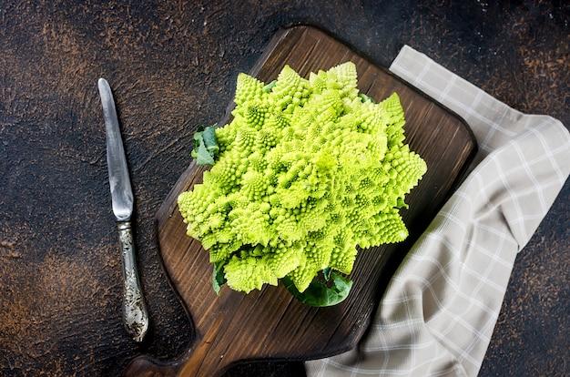 新鮮な緑のロマネスコ、暗い木製の背景のまな板で調理する準備ができて生の有機キャベツ
