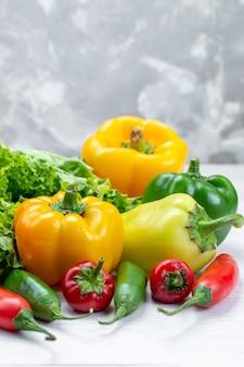 Insalata verde fresca con peperoni colorati e peperoni piccanti sulla scrivania leggera