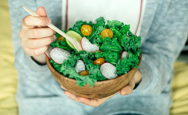 Свежий зеленый салат в деревянной миске.