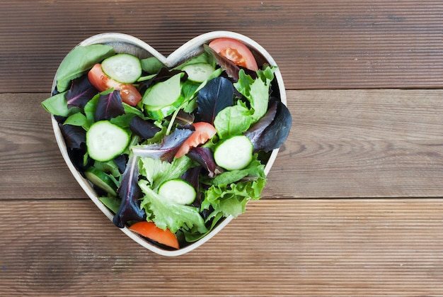 Fresh green salad mix in heart shaped plate.