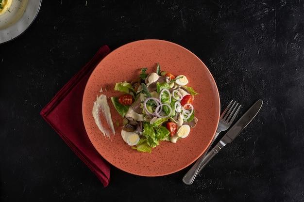 Свежий зеленый салат с говяжьим языком, помидорами черри, луком, перепелиным яйцом и грибами в красной тарелке.