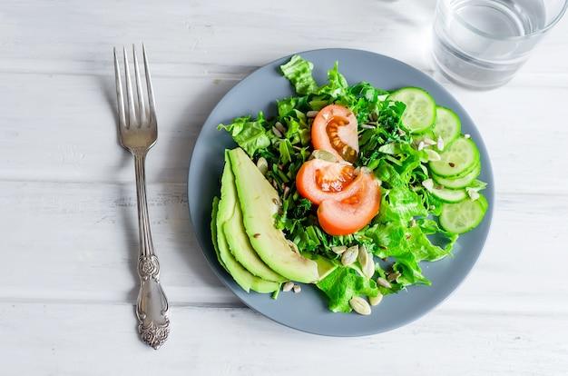 きゅうり、レタス、アボカド、トマト、グラスウォーターのフレッシュグリーンサラダ