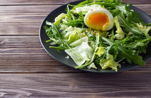 木製の背景に卵と新鮮なグリーンサラダ。