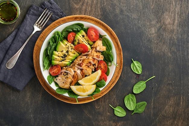 구운 치킨 필레, 시금치, 토마토, 아보카도, 레몬, 검은 참깨를 오래된 나무 어두운 탁자 배경에 있는 흰색 그릇에 넣은 신선한 녹색 샐러드. 영양 다이어트 개념입니다. 평면도 .