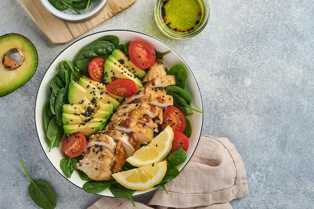 グリルした鶏ササミ、ほうれん草、トマト、アボカド、レモンと黒ゴマ、明るいスレートの背景に白いボウルにオリーブオイルを添えた新鮮なグリーンサラダ。栄養ダイエットのコンセプト。上面図。コピースペース