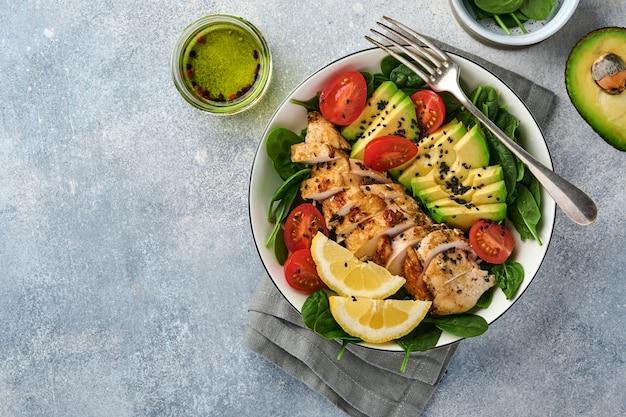 구운 치킨 필레, 시금치, 토마토, 아보카도, 레몬, 검은 참깨를 곁들인 신선한 그린 샐러드와 올리브 오일을 밝은 슬레이트 배경의 흰색 그릇에 담습니다. 영양 다이어트 개념입니다. 평면도