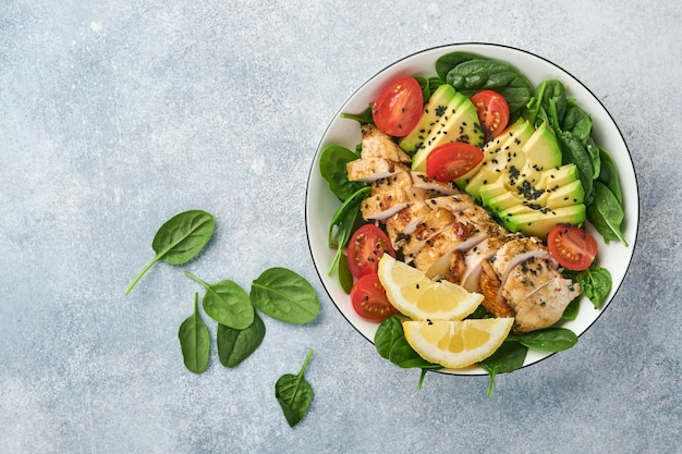 Fresh green salad with grilled chicken fillet, spinach, tomatoes, avocado, lemon and black sesame seeds, olive oil in white bowl on light slate background. nutrition diet concept. top view. copy space