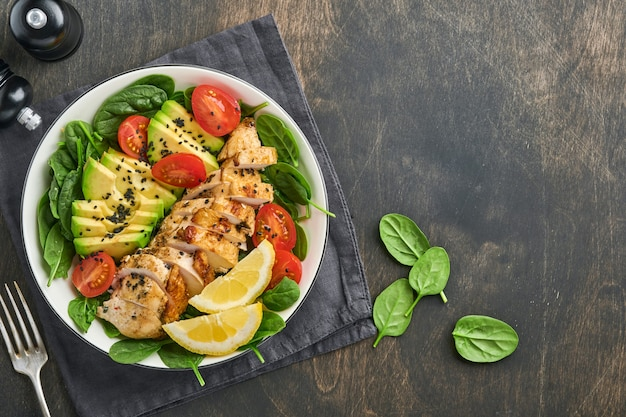 Fresh green salad with grilled chicken fillet, spinach, tomatoes, avocado, lemon and black sesame seeds in white bowl on old wooden dark table background. nutrition diet concept. top view .