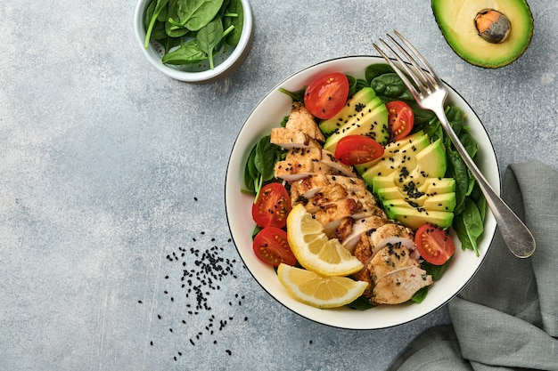 Fresh green salad with grilled chicken fillet, spinach, tomatoes, avocado, lemon and black sesame seeds with olive oil in white bowl on light slate background. nutrition diet concept. top view.