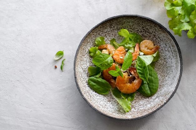 新鮮なグリーンサラダとエビフライの葉とレモンのクローズアップ皿とコピースペースの上面図