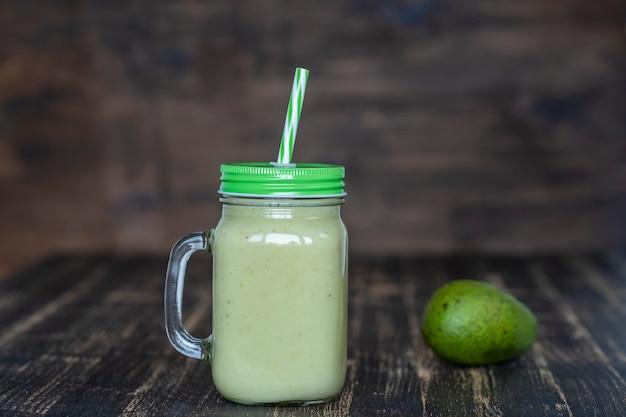 木製の背景にガラスのマグカップでアボカド、バナナ、蜂蜜からの新鮮な緑のスムージーをクローズアップ。健康的な食事の概念