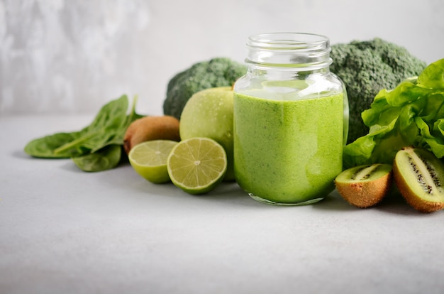 Fresh green smoothie in a jar with ingredients on a gray concrete background, selective focus.