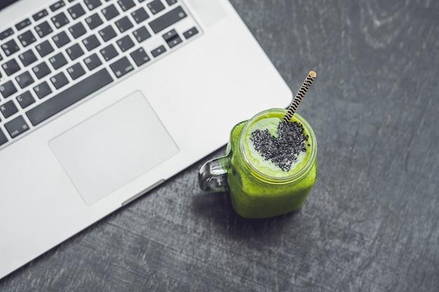 バナナとほうれん草の新鮮なグリーンスムージーとゴマの心とラップトップ健康的なローフードのコンセプトへの愛