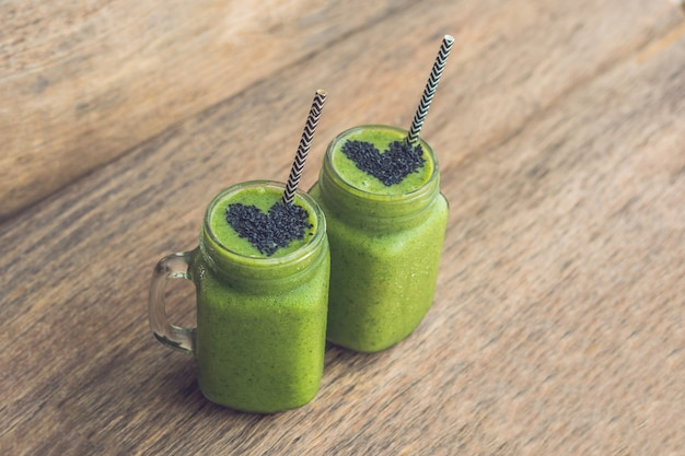 Fresh green smoothie with banana and spinach with heart of sesame seeds