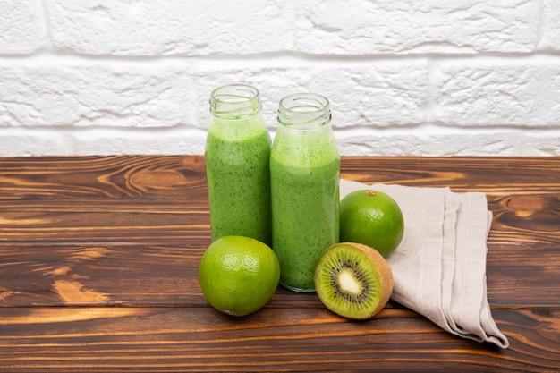 Свежий зеленый коктейль с хлопьями. зеленый коктейль смузи из шпината в стакане. молочный коктейль из шпината на светлом фоне. сок смузи на деревянном столе с хлопьями и киви. зеленый детокс-смузи.