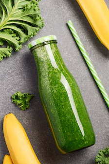 Fresh green smoothie with kale and banana in a bottle, top view.