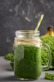 Fresh green smoothie with kale and banana in a jar.
