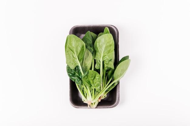 有機食品に詰められた新鮮な緑のほうれん草、健康的なライフスタイル。上面図