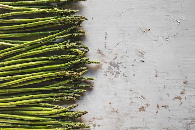木製の背景に新鮮な緑の春のアスパラガス。アスパラガスの季節