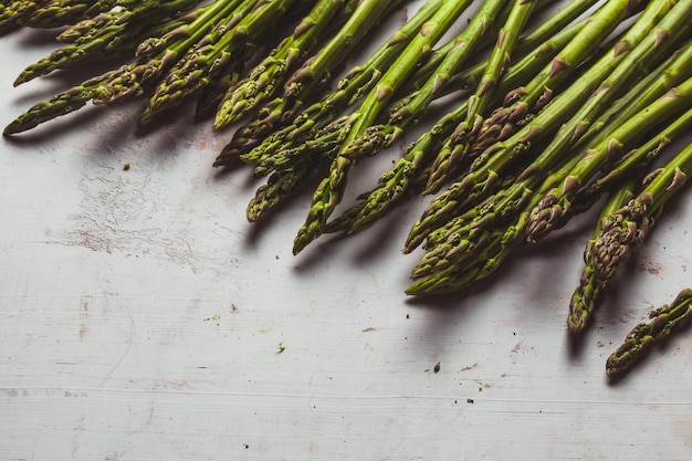 Fresh green spring asparagus on a wooden background