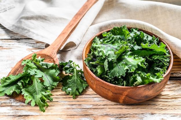 木製のボウルに新鮮な緑のスーパーフードケールの葉。有機ベジタリアン料理。白色の背景。上面図。