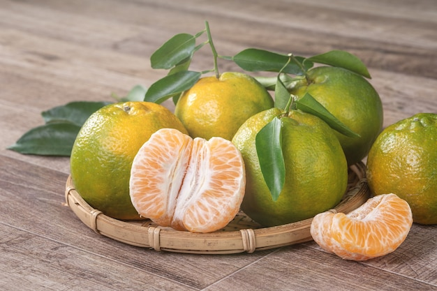 Fresh green tangerine mandarin orange with fresh leaves on dark wooden table background harvest concept.