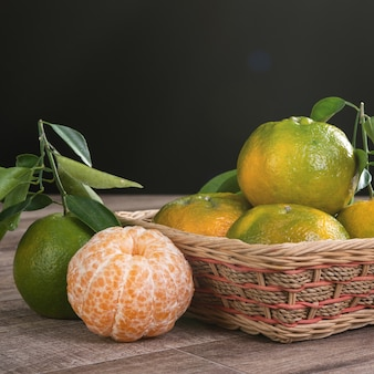 Fresh green tangerine mandarin orange with fresh leaves on dark wooden table harvest concept.