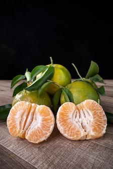 暗い木製のテーブルの背景の収穫の概念に新鮮な葉を持つ新鮮な緑のタンジェリンマンダリンオレンジ。