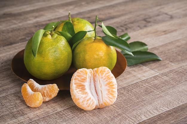 Свежий зеленый мандарин мандариновый апельсин со свежими листьями на концепции урожая предпосылки темного деревянного стола.