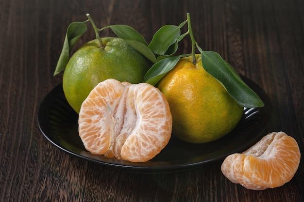ダークウッドのテーブル収穫のコンセプトに新鮮な葉を持つ新鮮な緑のタンジェリンマンダリンオレンジ。