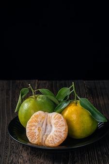 黒の背景の収穫の概念を持つ暗い木製のテーブルに新鮮な葉を持つ新鮮な緑のタンジェリンマンダリンオレンジ。