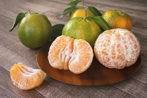 Fresh green tangerine with leaves on dark wooden table background