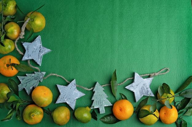 Свежие зеленые мандарины с ветвями и листьями на зеленом