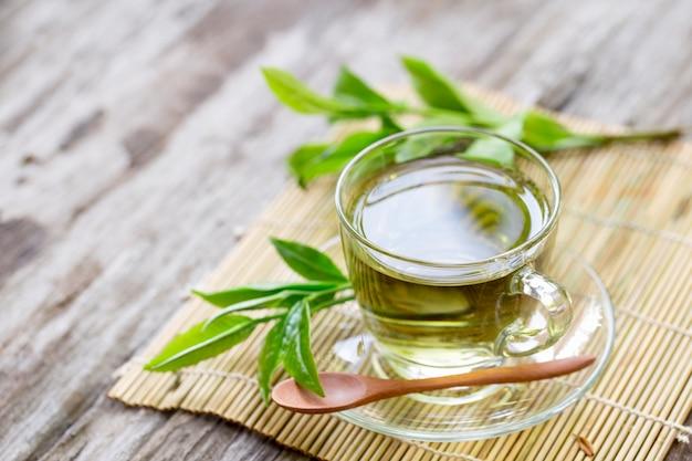 木のテーブルの上の水に茶葉と新鮮な緑茶