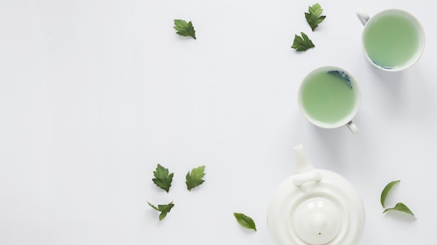 Fresh green tea with tea leaves and teapot on white background