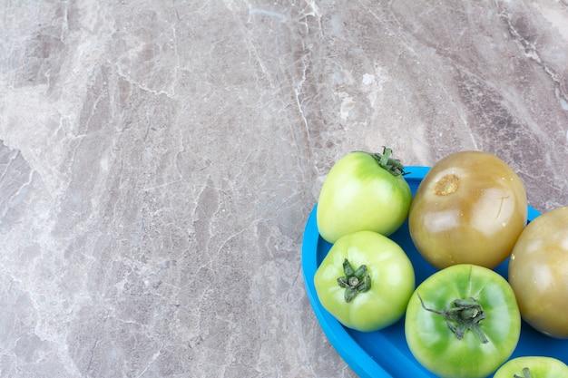 Pomodori verdi freschi e pomodori marinati sulla zolla blu.