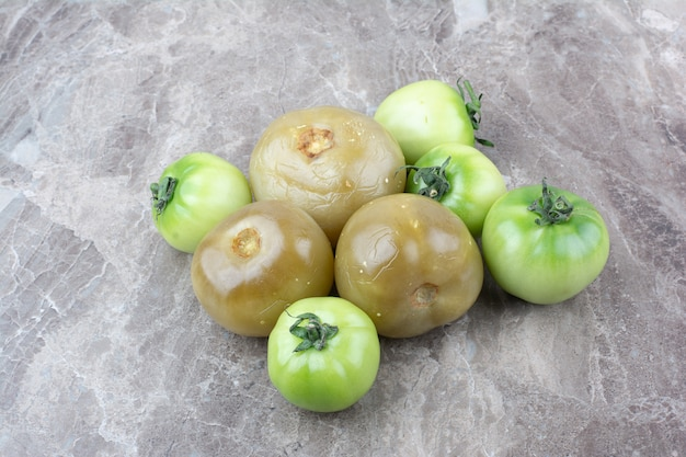 Fresh green tomatoes and pickled tomatoes on marble surface.