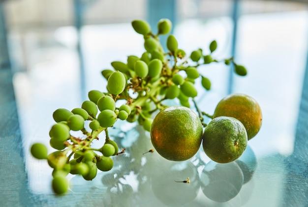 新鮮な緑の熟していないブドウと反射とガラスの背景にみかん