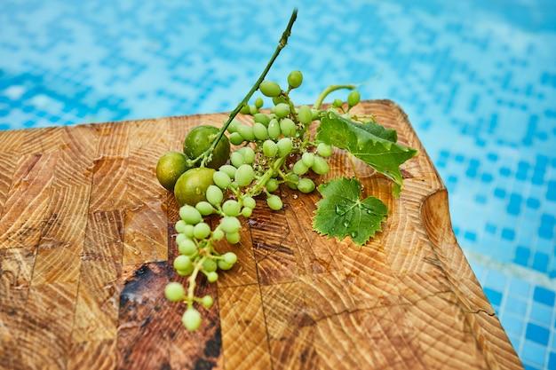 新鮮な緑の熟していないブドウ、みかん、青い水の中の木製の背景にマンゴー