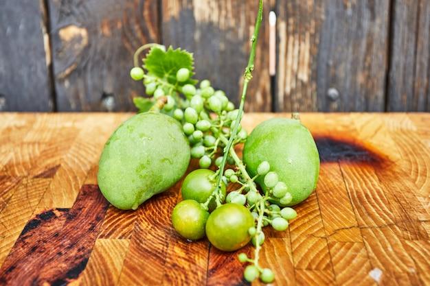 新鮮な緑の熟していないブドウ、みかん、木製の背景にマンゴー