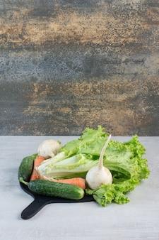 Свежие зеленые овощи и морковь на черной доске. фото высокого качества