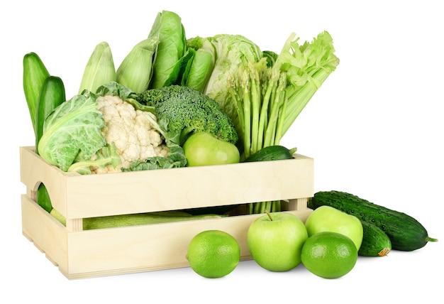 Свежие зеленые овощи и фрукты в деревянном ящике на белом изолированном фоне