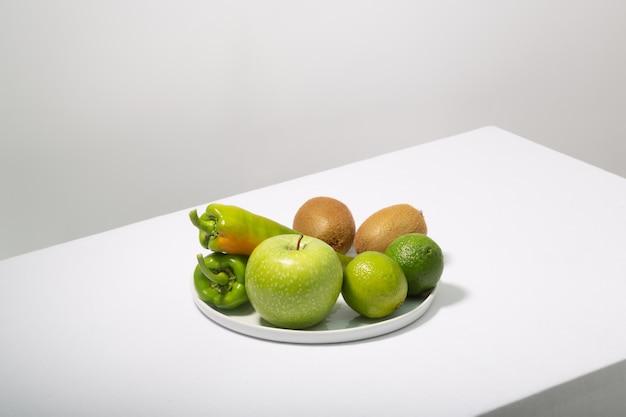 新鮮な緑の野菜と果物の白いテーブル。アルカリ食のコンセプト